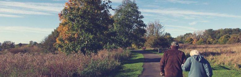 Valokuva ikääntyvästä parista kävelemässä puistossa.