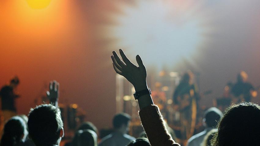 Yleisöä konsertissa. Lavalla musiikkiesitys.