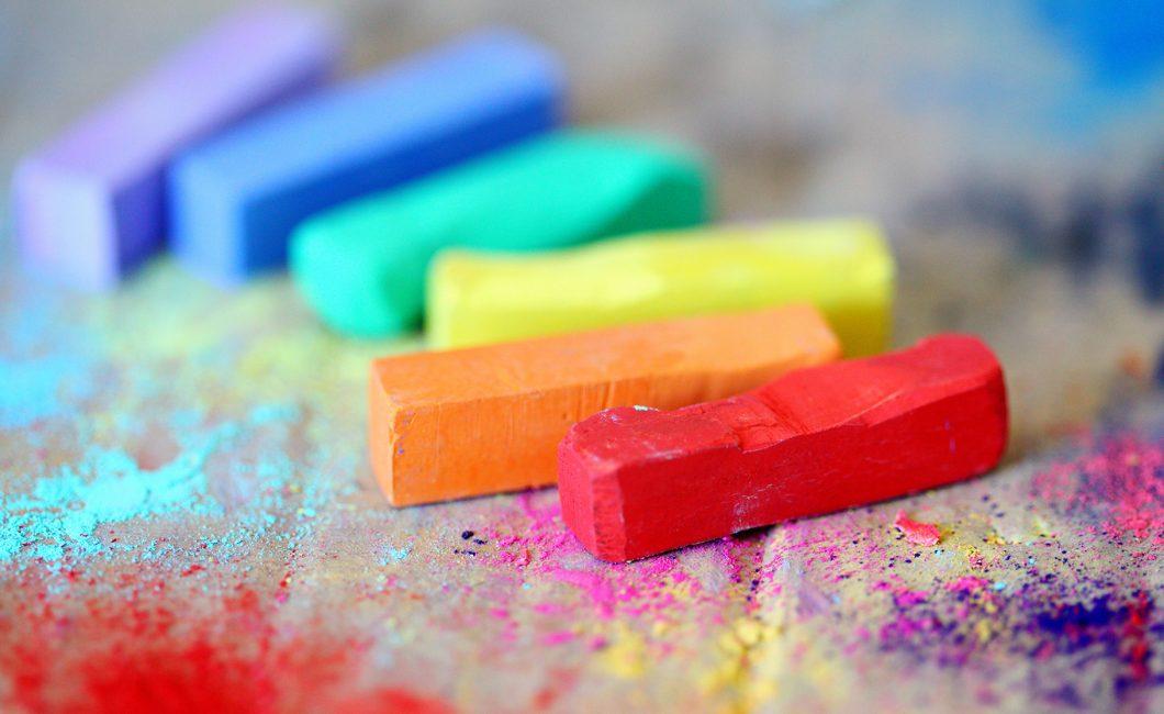 Värikkäitä liituja paperin päällä.