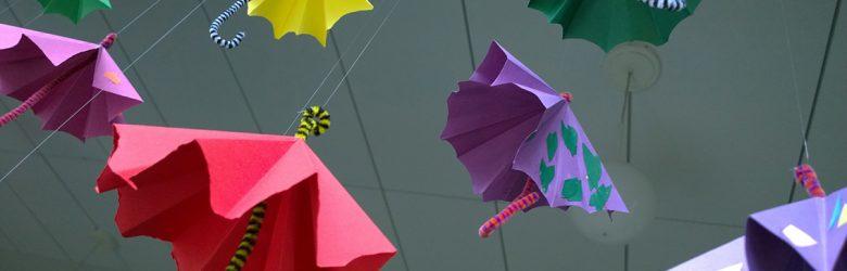 Värikkäitä paperista tehtyjä pieniä sateenvarojaj, jotka roikkuvat katosta. Kuva otettu alaviistosta.