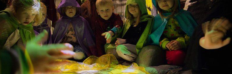 Erivärisiin hupullisiin viittoihin pukeutuneita lapsia istumassa ja seisomassa kelta-vihreän valaistun kangasmaisen lattialla olevan, hieman hohtavan elementin ympärillä. Lapsia näkyy kuvassa yhdeksän. Muutamat lapset heiluttavat käsiään. Kangasmainen pinta tuo mieleen veden, jossa on valkoisia kukkia.