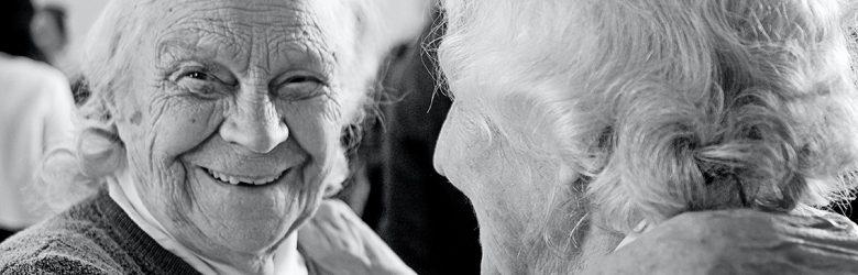 Kaksi vanhaa, valkohiuksista henkilöä tanssii tai halaa toisiaan kädet toistensa harteilla, kasvot lähellä toisiaan. Mustavalkoinen kuva, jossa on kuvattu vain ihmisten päät ja hartiat. Henkilöillä on hymy kasvoillaan.