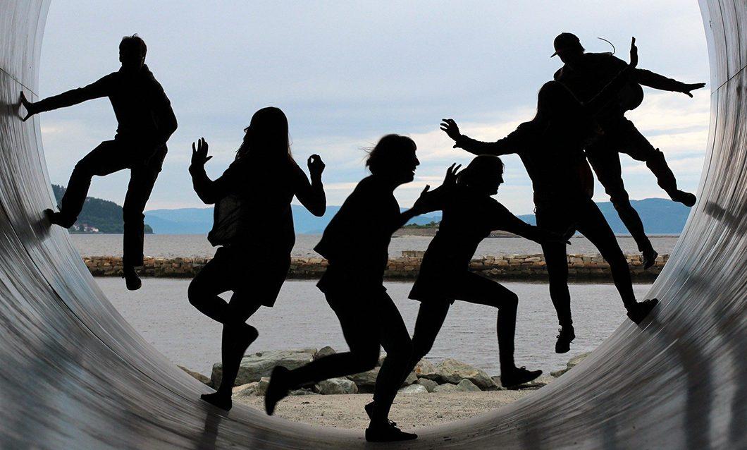 Kuusi ihmistä kuvattuna suuren kaarevan renkaan tai putken sisällä liikkumassa. Ihmiset on kuvattu silhuettimaisesti tummina hahmoina. Taustalla näkyy rantaa, vettä ja kukkuloita.